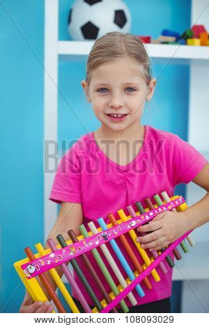 Smiling girl holding a xylophone at their desk