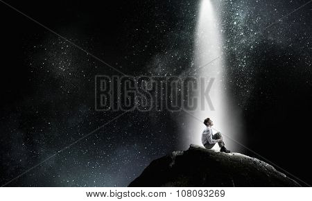 Young businessman sitting alone in light on rock top