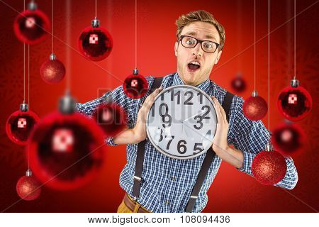Geeky businessman holding a clock against red snowflake background