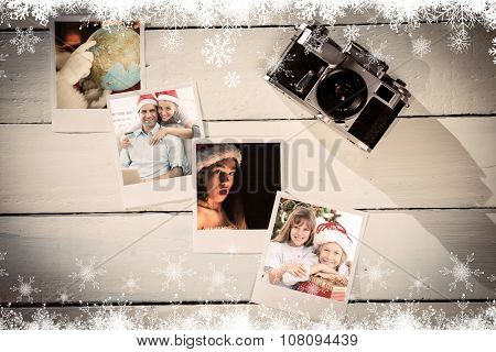 Happy couple in santa hats shopping online with laptop against instant photos on wooden floor