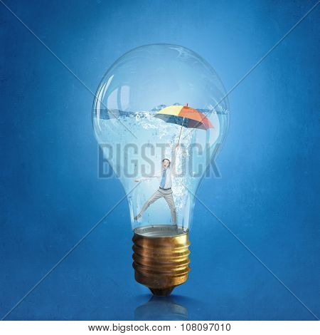Glass light bulb filled with clear water and businessman inside