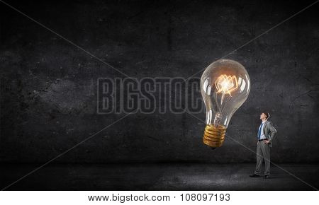 Young businessman in darkness looking at glowing light bulb