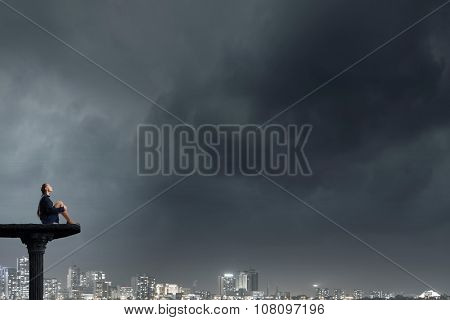 Bored young businesswoman sitting alone on top