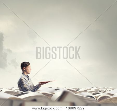 Young man sitting in pile of old books