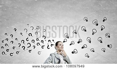 Young pensive businesswoman and ideas coming out of her head