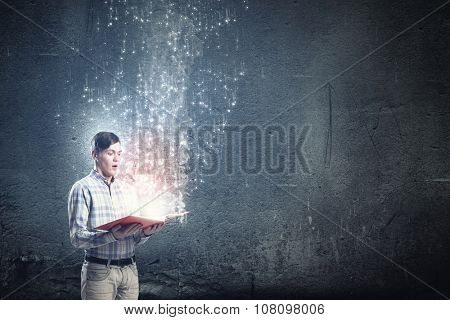 Close up of man holding opened book with flying out characters