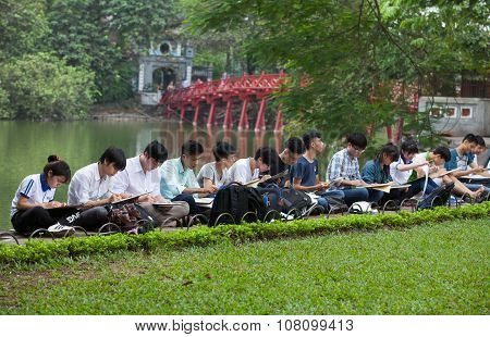 Asian fine art students practicing to draw at a green park