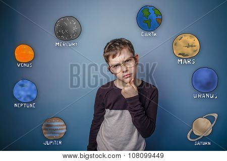 Teenage boy in glasses thinking planets of the solar system astr