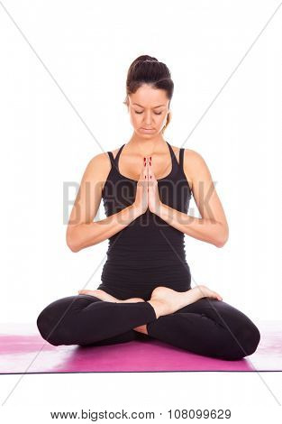 Beautiful woman doing Lotus of Padmasana or Kamalasana pose on yoga class. Studio shot.