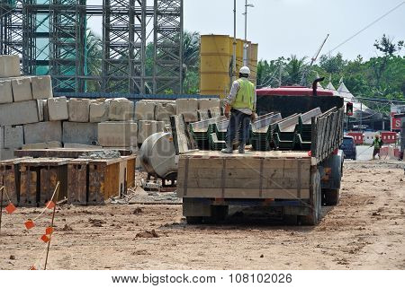 Construction workers unloading the sheet pile cofferdam of the lorry at a construction site