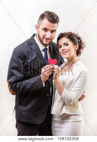 Cheerful young couple holding paper heart and smiling