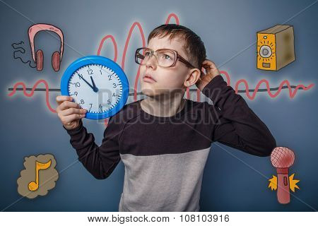 Teenage boy holding a watch and looks up scratching his head a s