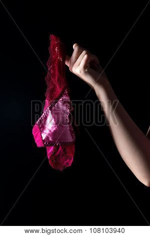 Hand and panties on black background