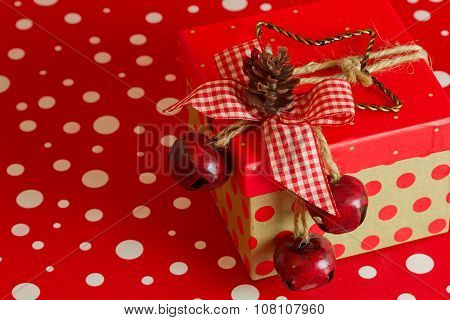 A Country Christmas Present Topped With A Pine Cone And Jingle Bells