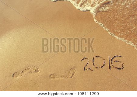 2016 year written and footprint on sandy beach sea.  Concept come new year. Toned image.