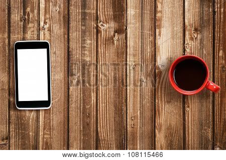 Mobile Phone And Coffee Cup On Wooden Table