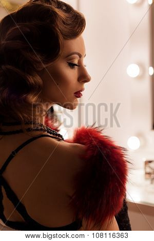portrait of a beautiful sexy young woman with retro hairstyle lace lingerie with fur sitting on the