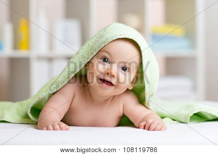Smiling baby after shower or bath with towel on head