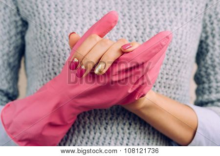 Woman In A Gray Sweater And Bright Manicure Wearing Pink Rubber Gloves To Clean The House.