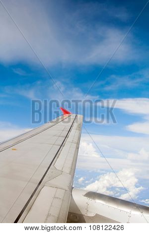 Airplane wing from window, clouds and blue sky background.