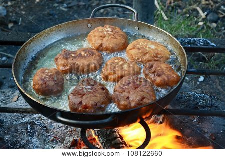 Patties Fried In A Large Frying Pan Over A Campfire In Marching Conditions