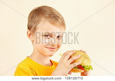 Little funny boy with tasty sandwich