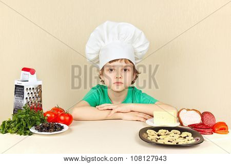 Little boy in chef hat at table with ingredients for pizza