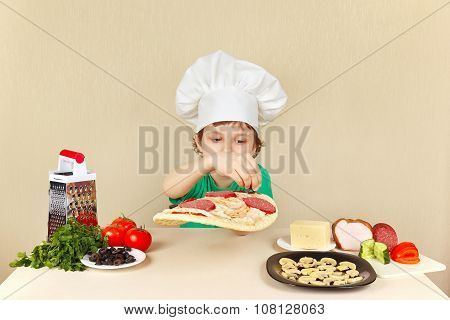 Little funny chef puts olives on pizza crust