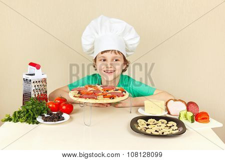 Little smiling boy in chefs hat preparing pizza