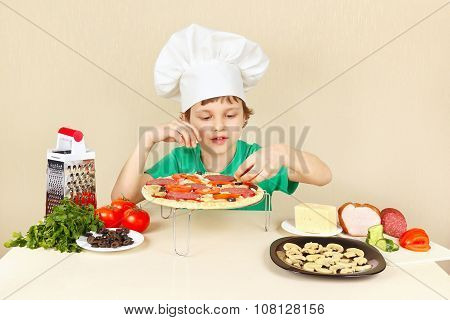 Little funny chef puts the ingredients on pizza crust