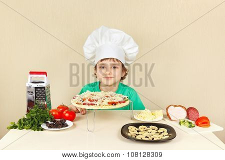 Little funny chef in chefs hat preparing pizza