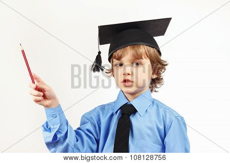 Little pensive boy in academic hat with pencil on white background