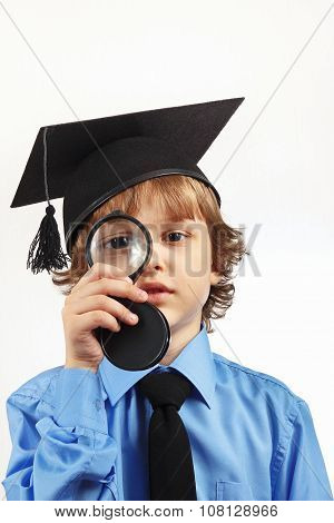 Little serious boy in academic hat with a magnifying glass on white background