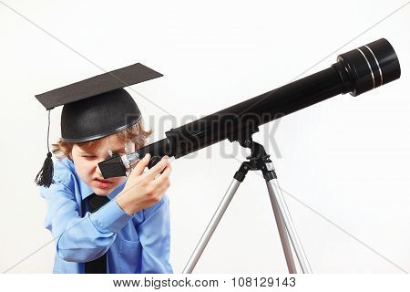 Little astronomer in academic hat looking through a telescope on white background
