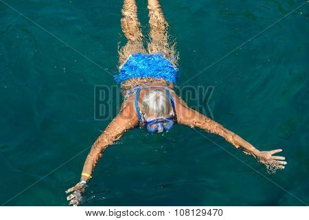 Aged Woman Is Swimming With Mask In The Sea Water.