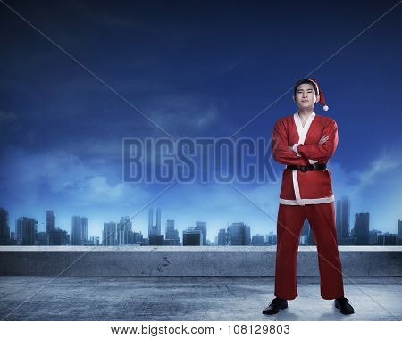 Asian Man In Santa Claus Costume Standing On Rooftop