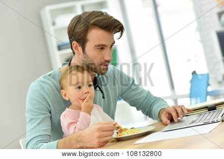 Man working from home and taking care of baby