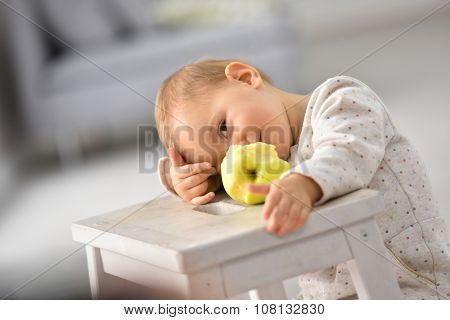 Cute 15-month-old baby girl eating an apple