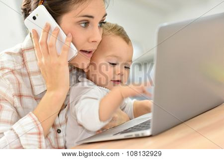 Busy young businesswoman working on laptop, baby on lap