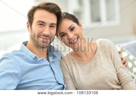 Young smiling couple sitting in sofa at home