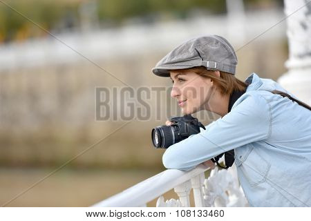 Young woman with photo camera admiring scenery over bridge