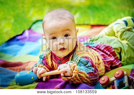 Cute Baby Boy Playing With A Wooden Rattle Toy
