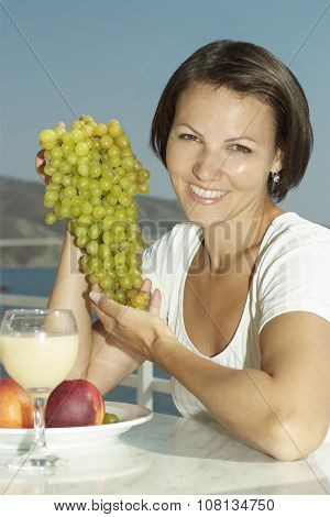 Happy young woman with grapes