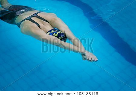 girl athlete in swimming start swimming under water