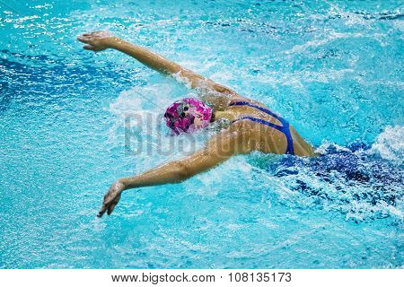 young woman athlete swims butterfly