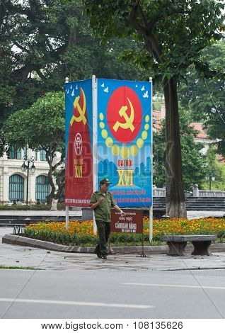 Security officer walking via a panel to propagate about a congress of the Communist Party of Vietnam