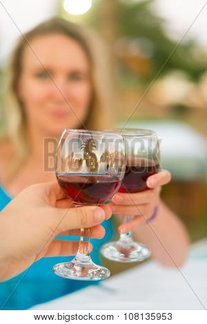 Man And Woman Clinking Their Glasses With Red Wine.