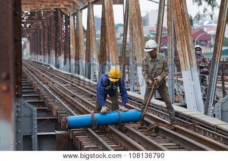 Asian bridge builders working on old vintage Long Bien bridge