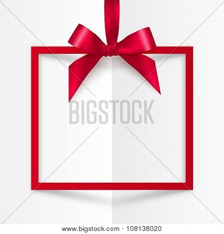 Red gift box frame with silky bow and ribbon on white folded paper background