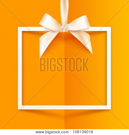 White gift box frame with silky bow and ribbon on orange folded paper background